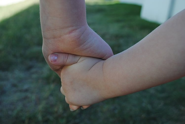 Image shows kids holding hands.