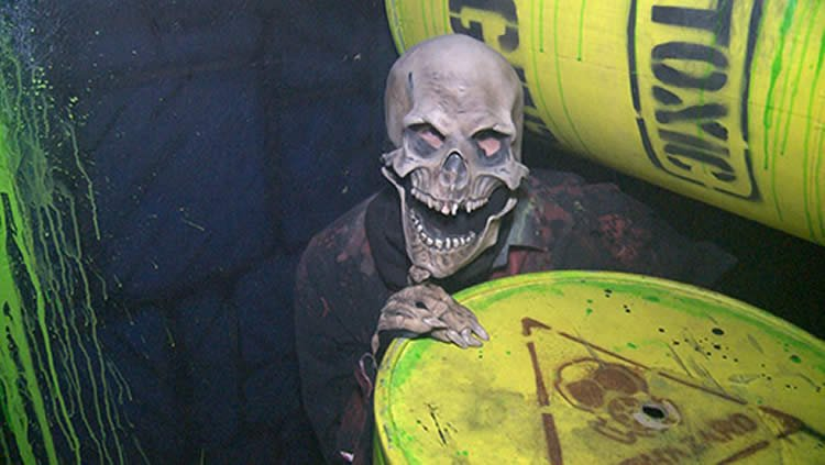 Image shows a skeleton hiding behind an oil drum.