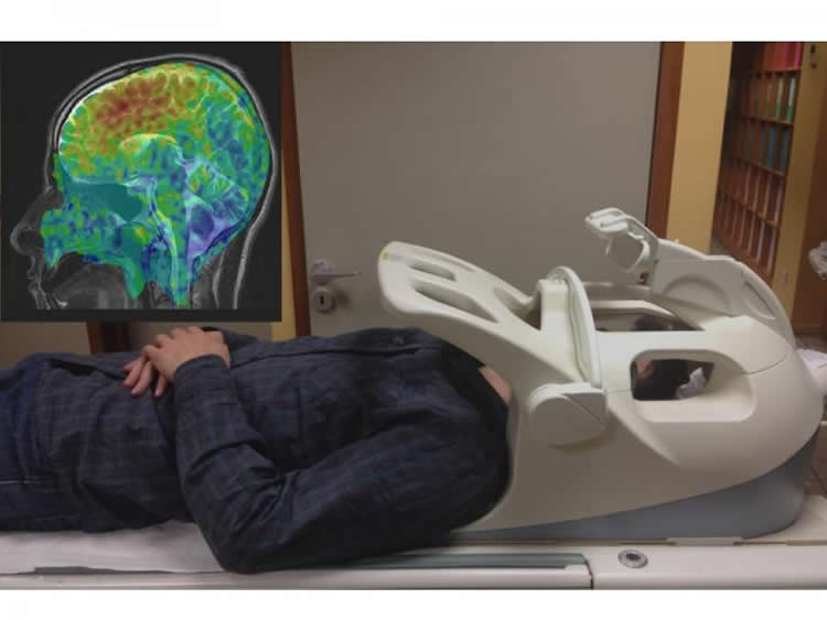 Image of a person in an MRI machine with a brain scan on a computer monitor at the side of him.