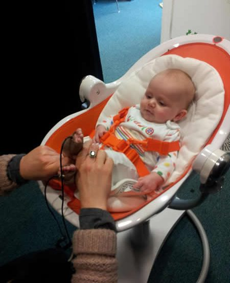 Photo of a little baby. Her feet are being tickled.