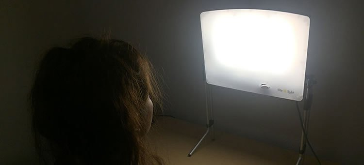 Image shows a woman sitting infront of a light box.