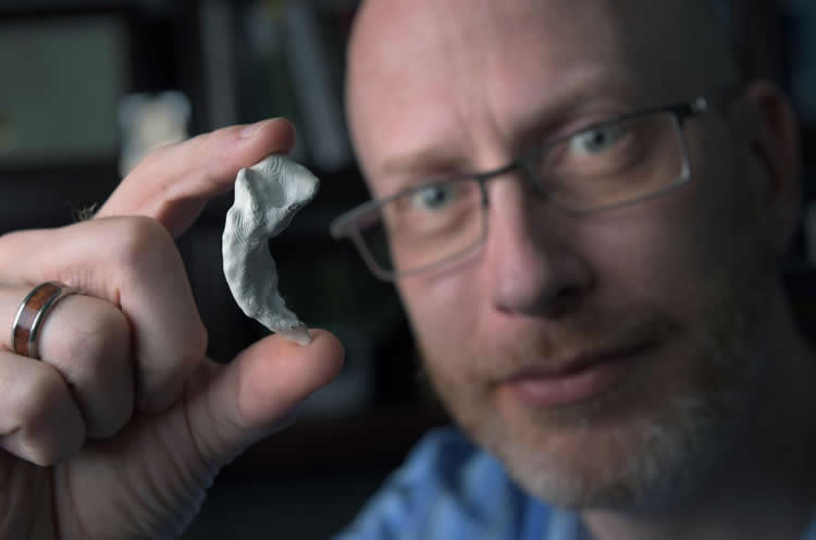 Photo of the researcher an a printed 3D model of his hippocampus.