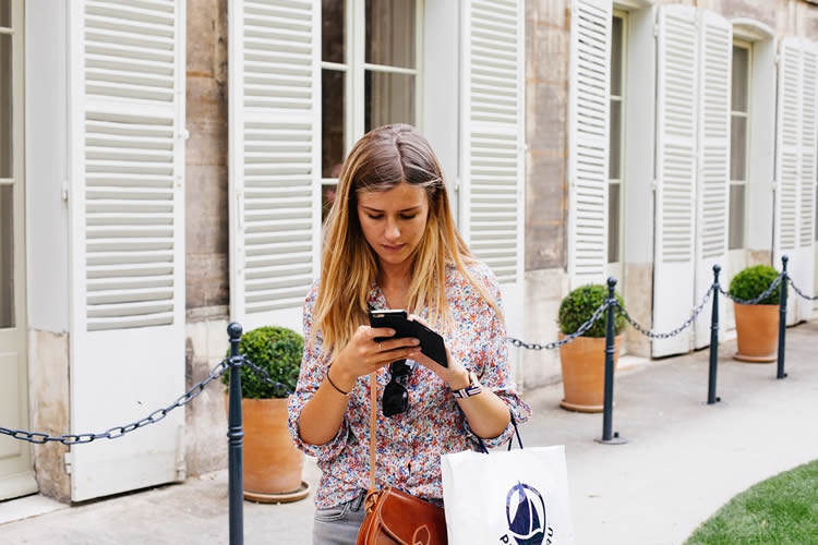 Image shows a girl walking and texting.