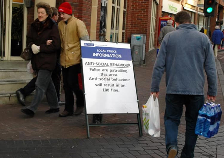 Image of people walking past an ASBO sign.