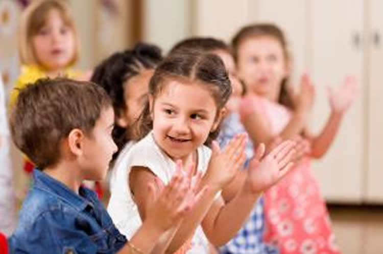 Image shows children playing a clapping game.