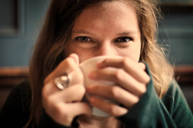 Image shows a woman drinking a cup of coffee.