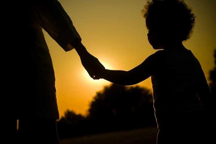 Image shows child holding its mom's hand.