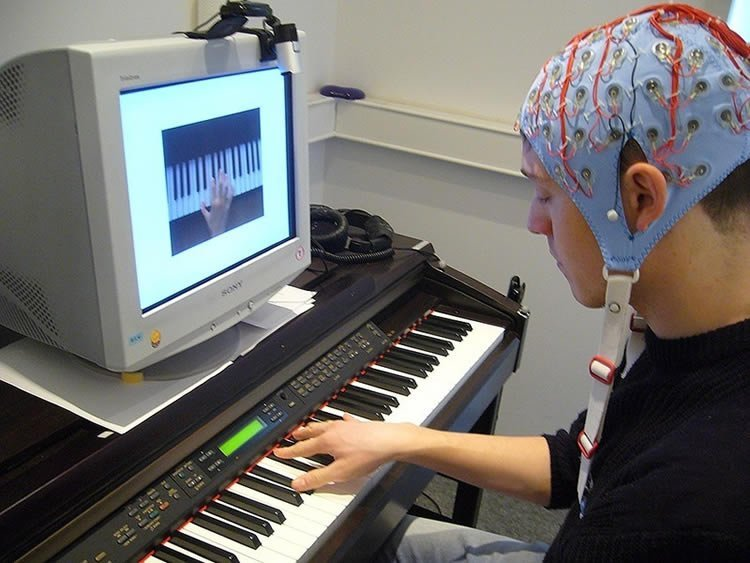 Image shows a man in an eeg cap playing piano.
