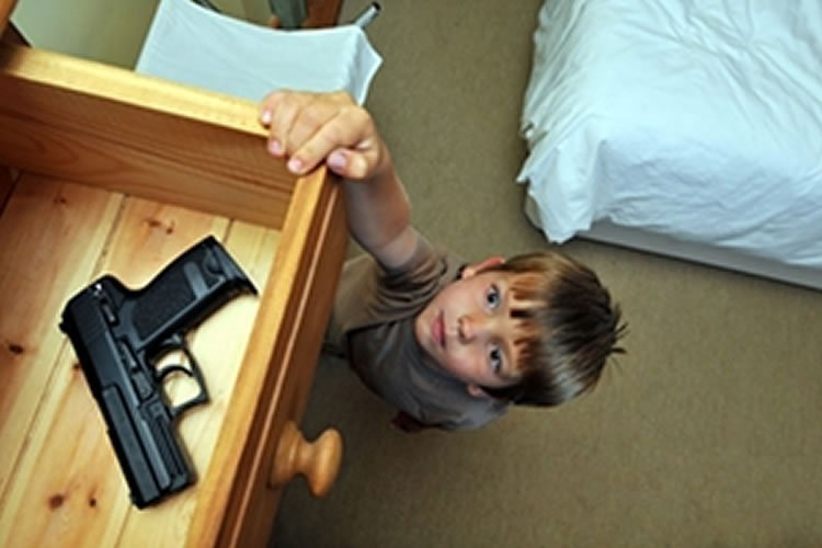 Image shows a little boy reaching for a gun in a draw.