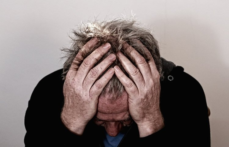Image shows an older man holding his head in despair.