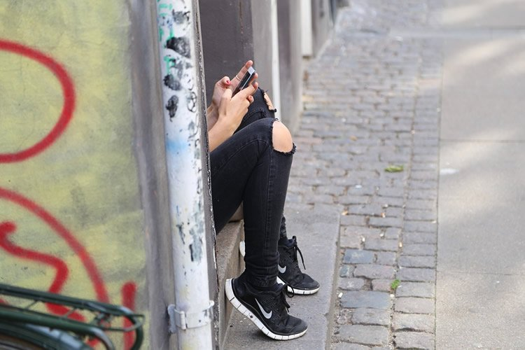 Image shows a girl search on a cell phone.