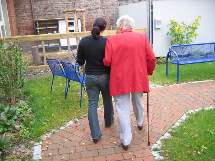 Image shows an old and young woman walking together.
