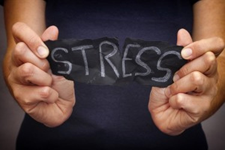 Image shows a woman ripping up a piece of paper with the word Stress written on it.