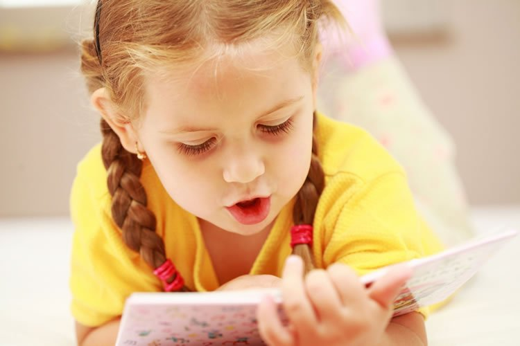 Image shows a little girl reading a book.