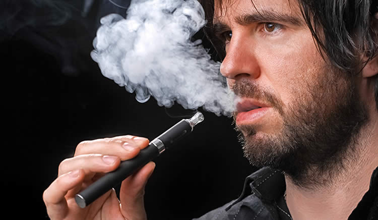 Image shows a man smoking an e-cig.