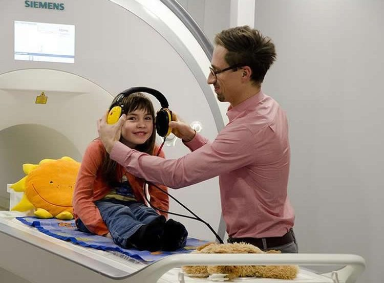 Image shows a little girl in headphones sitting on an MRI scanner bed.