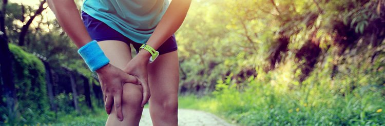 Image shows a runner clutching their knee in pain.