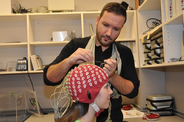 Image shows the research putting an EEG cap on a test subject.