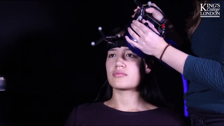 Image shows a woman undergoing rTMS.