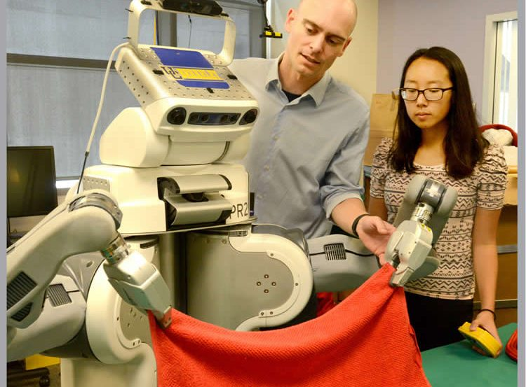 Image shows BRETT the robot folding a towel.