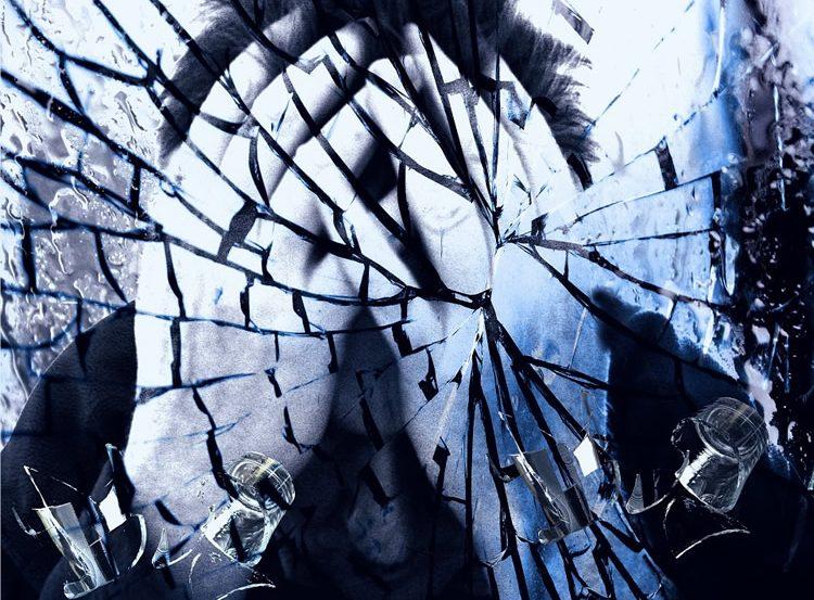 Image of a man behind broken glass.