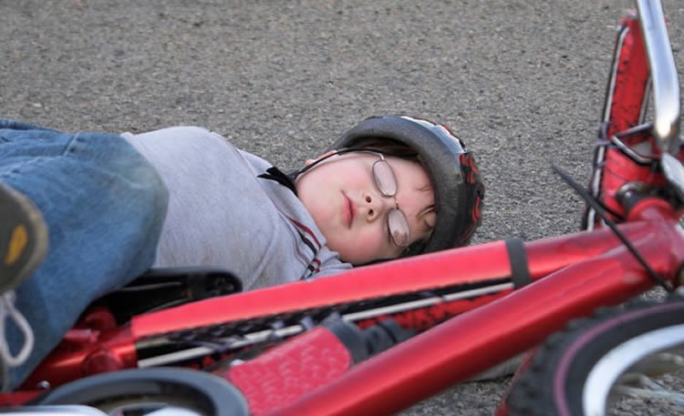 Photo of a child laying next to a bike.