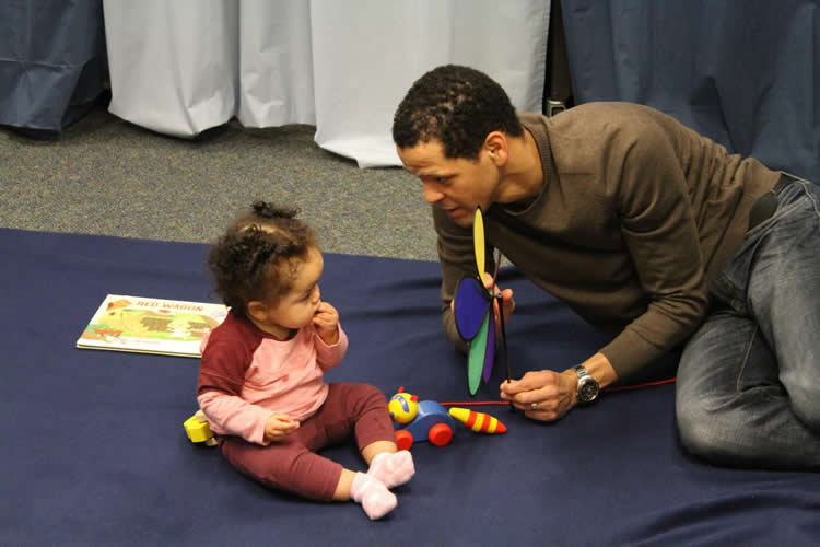 Image shows a researcher and baby.