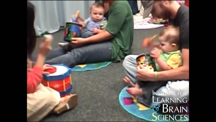 This image shows babies and parents playing drums.