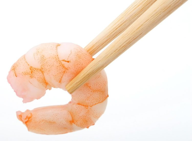 Image shows a shrimp being picked up with chopsticks.