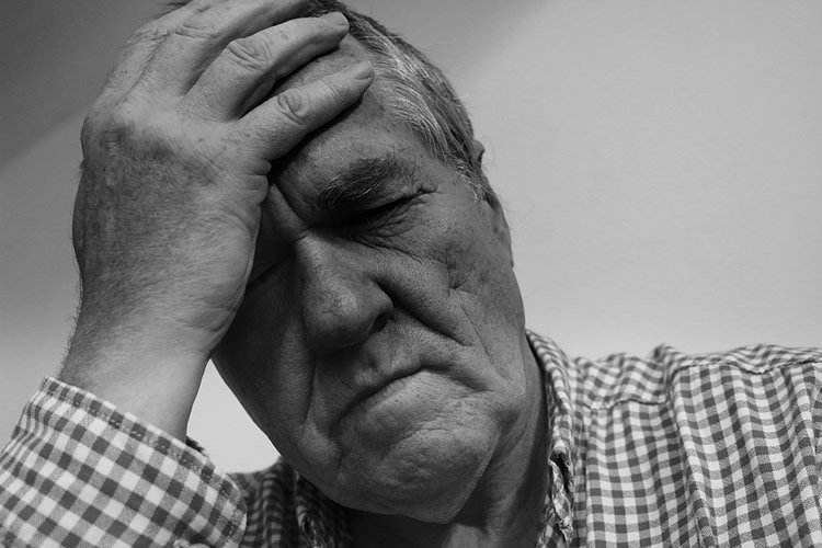 Image shows an older man holding his head in pain.