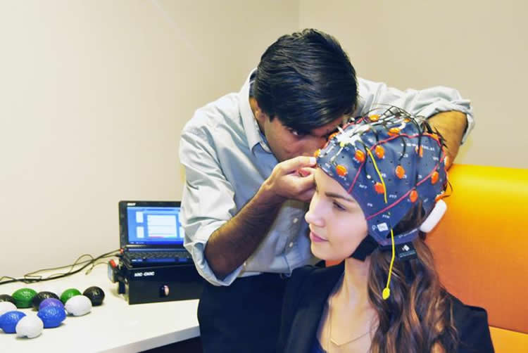 Image shows a girl in an EEG cap.