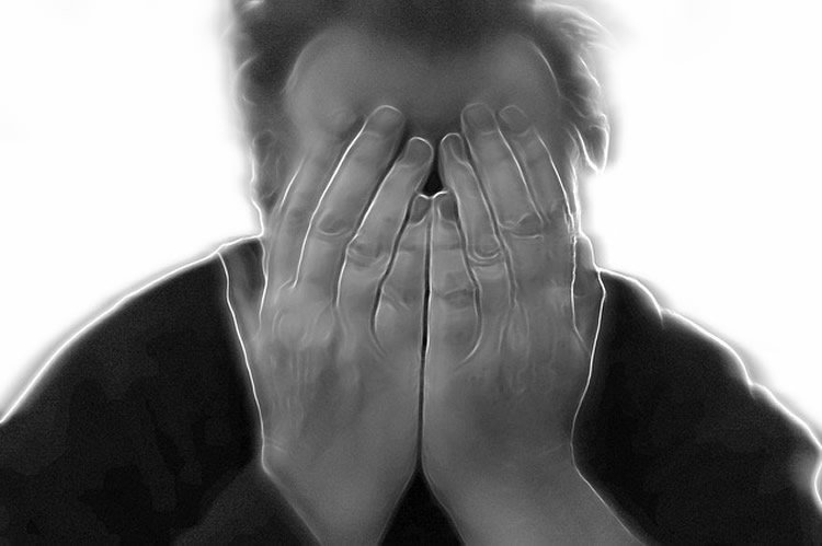 Image shows a man holding his head in pain.
