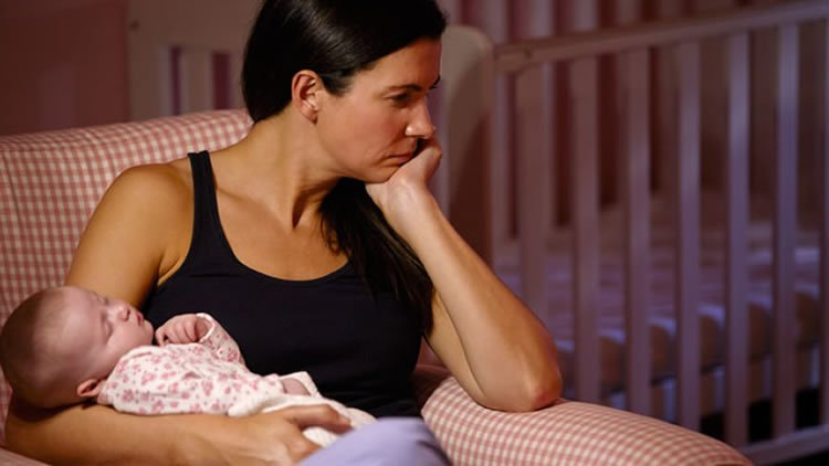 Image shows a depressed looking woman holding a baby.