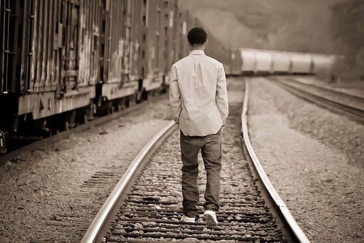 Image shows a teenaged boy walking along a railway track.