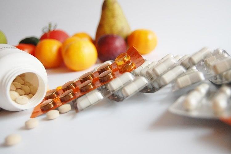 Image shows vitamin pills and fruits.