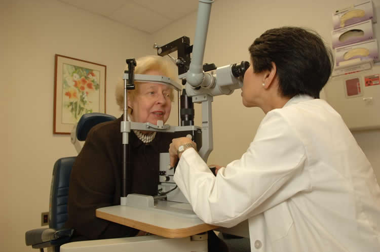 Image shows a doctor performing an eye exam.