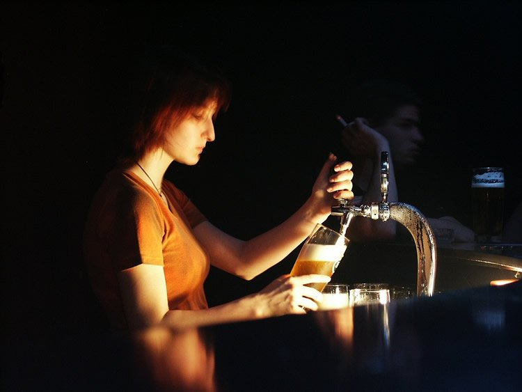 Image shows a woman serving beer.