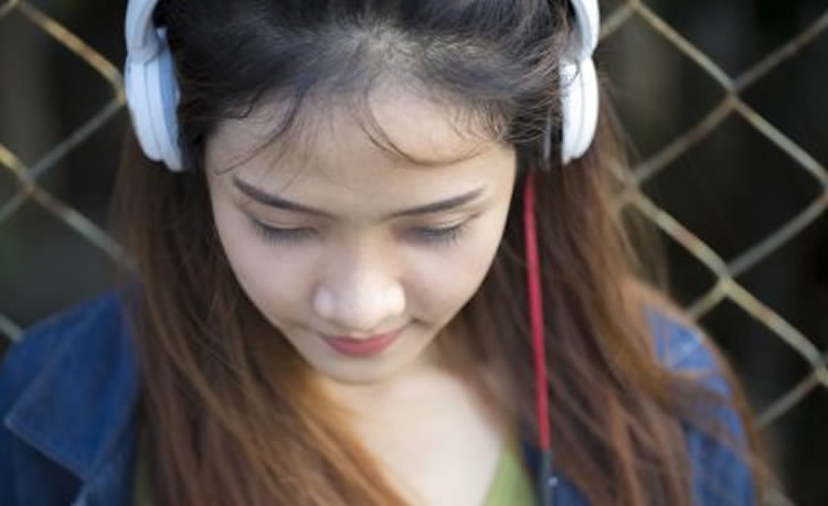 Image shows a girl with headphones on.