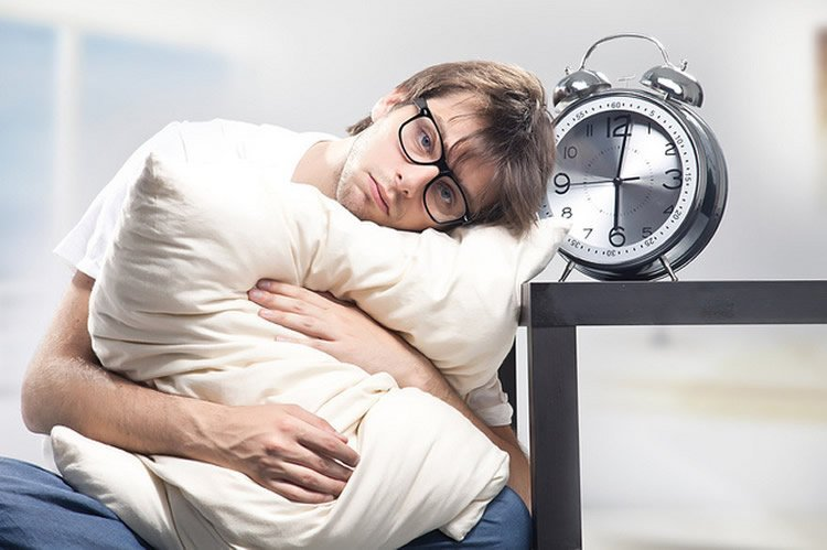 Image shows a sleepy looking man holding a pillow.
