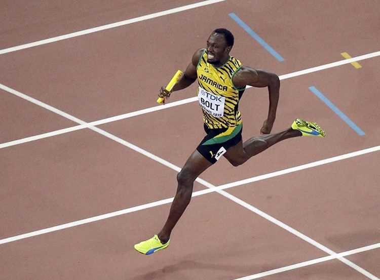 Image shows Usain Bolt running a relay race.