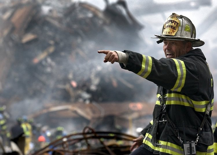 Image shows a fire fighter in the rubble of the twin towers.