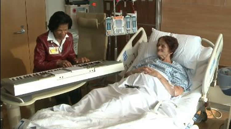 Image shows a woman olaying piano to a patient.