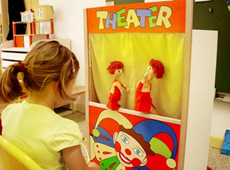 Image shows a child watching a pupet show.