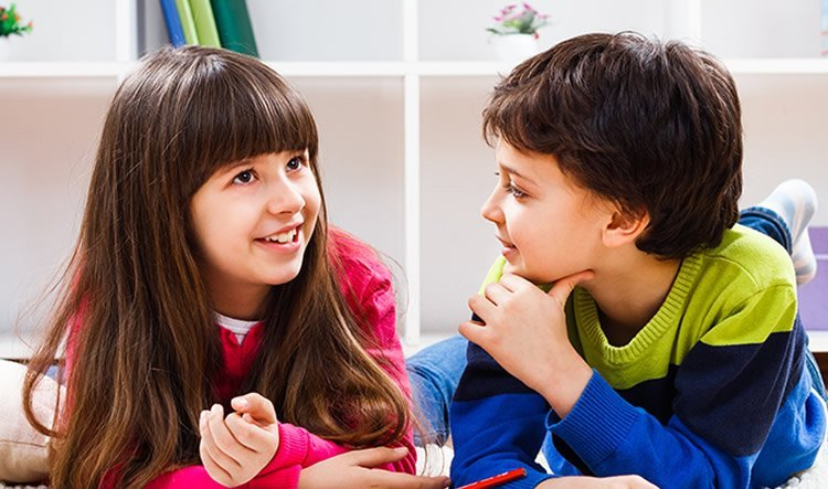 Image shows two children talking.