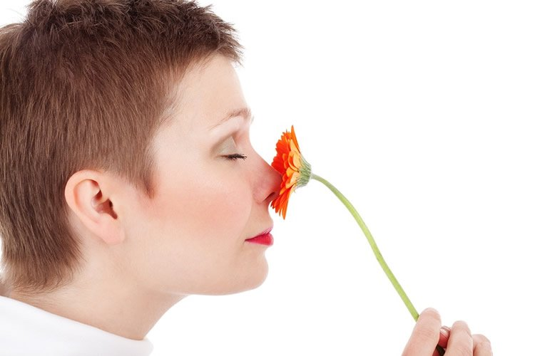 a woman smelling a flower.