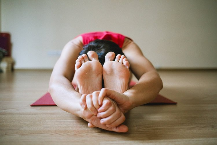 Image shows a person in a yoga pose.