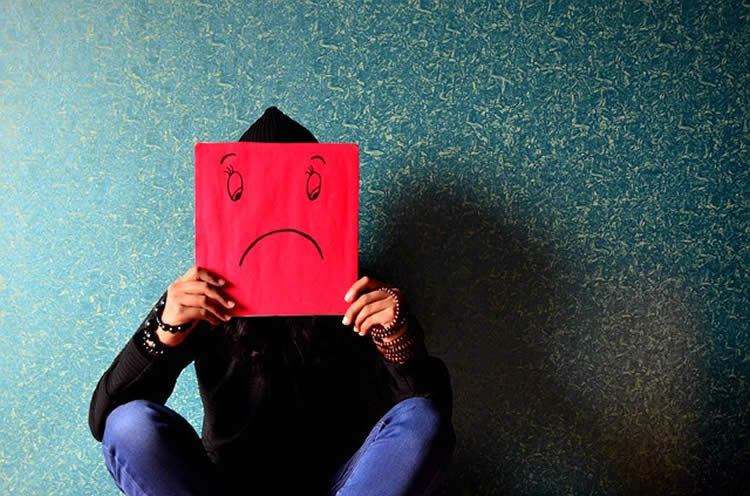 Image shows a person sitting next to a wall with a paper, sad face mask.