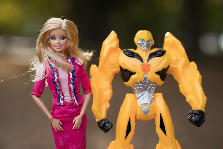 Image shows a Barbie doll and a Transformer toy.