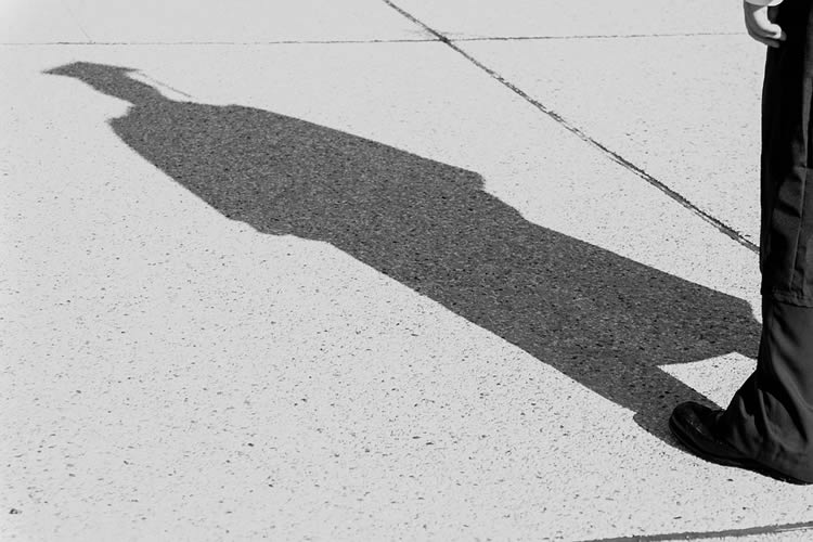 Image shows the shadow of a person in a cap and gown.