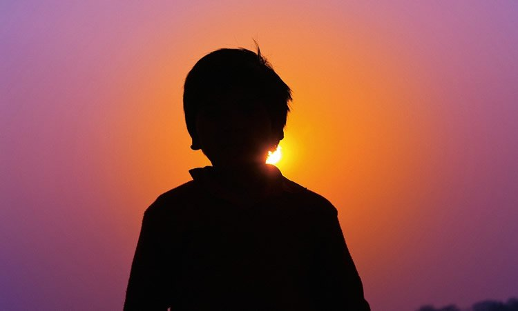 Image shows a teenage boy looking at a sunset.